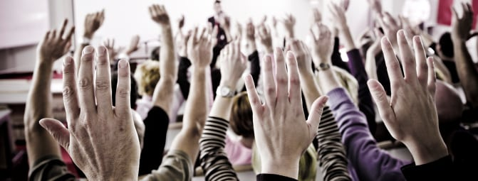 community organizing town hall in nh with hands raised